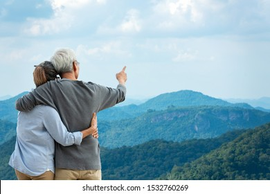 Asian Lifestyle senior couple hug and pointing the mountain nature.  Old people happy in love romantic and relax time. Tourism family elderly retirement travel in summer leisure and destination.