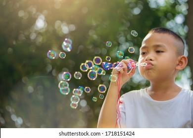Asian little boy is blowing a soap bubbles