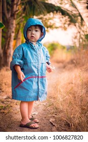 Asian Little boy in a blue jacket at autumn walking in a fores
