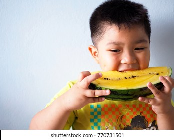 Asian little boy eating watermelon.