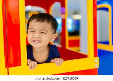Asian Little boy happy looking through window. He travels on a train.