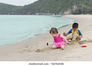 Asian little boy and his baby sister playing together on the sandy beach.