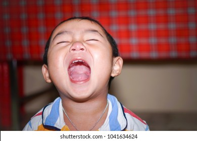 The asian little boy is laughing.