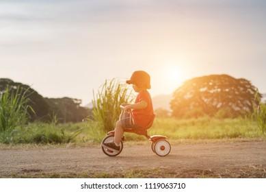 Asian little boy on  bike.
