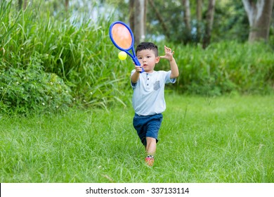 Asian little boy playing tennis at outdoor