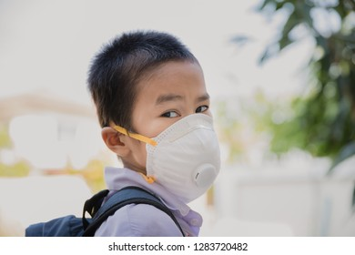 Asian little boy in school uniform and wearing N95 mask while walking in garden in the city