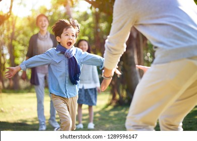 asian little boy son running towards father's embrace.