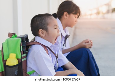Asian little boy in student uniform has drowsiness in the morning of school start day