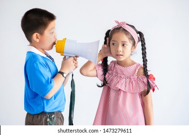 Asian  little boy talking to his sister through a megaphone, girl puts a hand to the ear to hear better, over white background