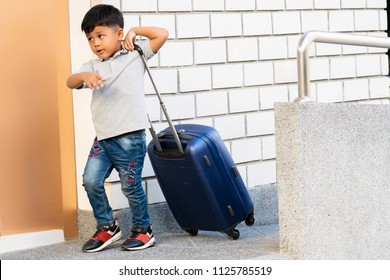 Asian little boy was walking to travel, kid drag bag