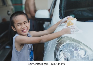 Asian little boy is washing the car, helping his father on holiday