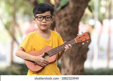 An Asian little boy wearing glasses is happily playing the ukulele. Asian little child is trying to play the ukulele with a fully happy moment.