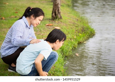 Asian little child girl about to throw up,vomit,puke retch barf,feeling sick from indigestion or food poisoning,stomach upset virus,cute daughter with woman or mother helping,care her in outdoor park