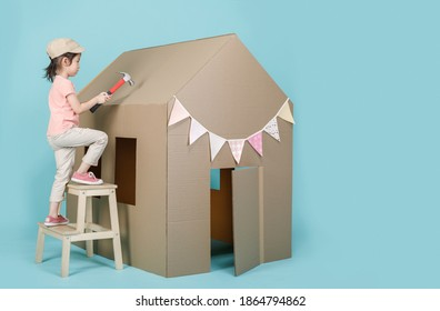 Asian little child girl building her cardboard house isolated on blue long banner with copy space for your text, Creative at home with family concept