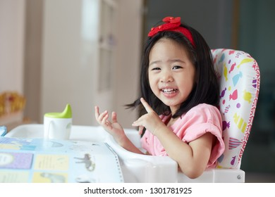 Asian Little child girl eating breakfast on high chair very happy, she yummy