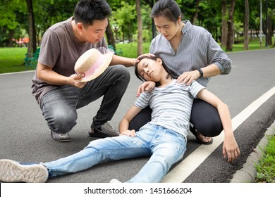Asian little child girl with heat stroke,high temperature,sick daughter having exhausted suffering from sunburn very hot in summer outdoor, feeling faint,father and mother assisting