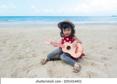 Asian little child girl playing guitar or ukulele on the beautiful beach in summer season. Music,musician and guitarist concept