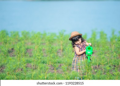 Asian little child girl pouring water on the trees. kid helps to care for the plants with a watering can in the garden.