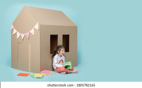 Asian little child girl reading a book with cardboard house isolated on blue long banner with copy space for your text, Homeschooling during the Coronavirus (COVIC-19) concept