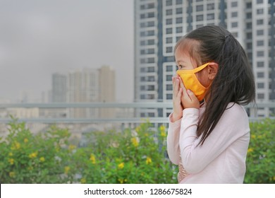 Asian little child girl wearing a protection mask against PM 2.5 air pollution in Bangkok city. Thailand.