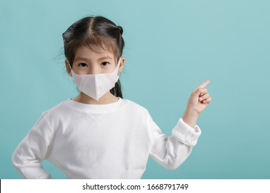 Asian little child girl wearing respirator mask to protect coronavirus outbreak and pointing hand to blank background, New virus Covid-19 from Wuhan China concept, Empty space isolated on blue