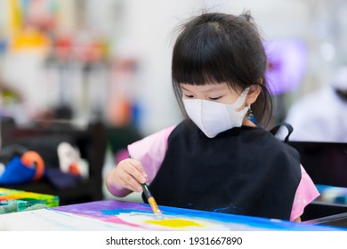 Asian little child girl wearing a 3D surgical face mask. Children learn art and paint on canvas. Kid wears a black apron. Happy study in a combined class. Pupil aged 4 years old.