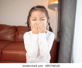 Asian little children blow her nose while sneezing