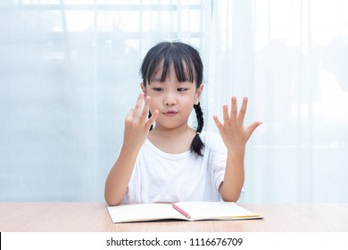 Asian little Chinese Girl doing mathematics by counting fingers at home
