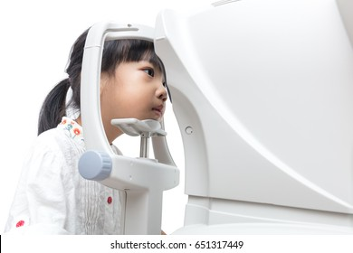 Asian Little Chinese Girl Doing Eyes Examination Through Auto refractometer in isolated White Background