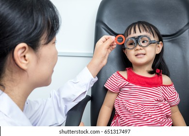 Asian Little Chinese Girl Doing Eyes Examination by ophthalmologist at An Optical Shop