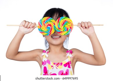 Asian Little Chinese girl holding lollipop in isolated white background