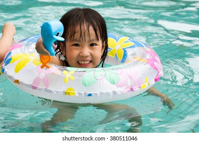 Asian Little Chinese Girl Playing in Swimming Pool with Swimming Circle