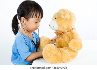 Asian Little Chinese Girl Playing Doctor with Teddy Bear isolated on white background