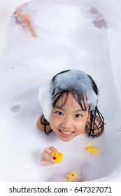 Asian little Chinese girl playing with water and foam in bathtub at home