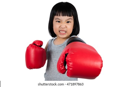 Asian Little Chinese Girl Wearing Boxing Glove With Fierce Expression in isolated white background.