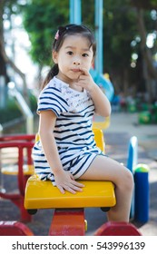 Asian little cute girl with curly hair in the park