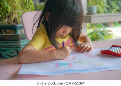 Asian little cute girl drawing picture. Drawing is play therapy for ADHD kids (Attention deficit hyperactivity disorder),can be used to address emotional problems.