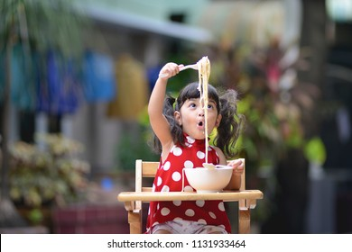 Asian little cute girl have fun while eating Italian spaghetti  white sauce or carbonara on the table in outdoor. kid have fun and joyful with eating