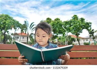Asian little cute girl kid student in uniform school reading a book sitting on the wooden bench in the park with cloud and blue sky background.Education study learning and success literacy concept.