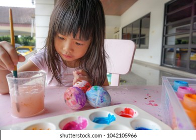 Asian little cute girl painting on easter eggs. Painting is play therapy for ADHD kids (Attention deficit hyperactivity disorder),can be used to address emotional problems.