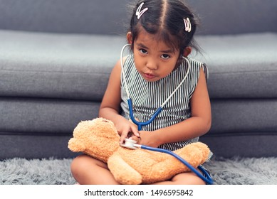Asian little cute girl playing doctor or nurse with listens a stethoscope plush toy bear on gray carpet at home.Medical concept.,retro vintage color tone.
