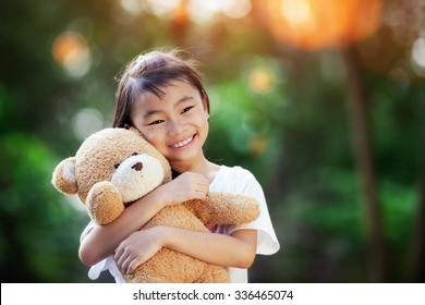 Asian Little cute girl standing in the grass holding large teddy bear with sunset light