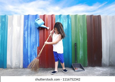 Asian little cute girl sweeping the floor with broom at outdoor on colourful wall and blue sky background.Inspired kid doing household chore.People,Housework, cleaning and housekeeping concept.