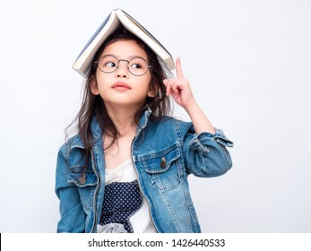 Asian little cute girl wearing glasses and put the book on head. Preschool lovely kid with the book covering on her head and pointing finger up. Learning and education of kid.