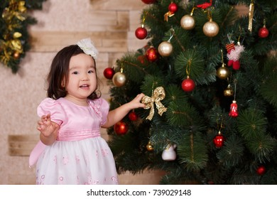 Asian little cute girl wearing casual dress posing close to new year christmas green classic tree with balls toys and colourful presents.Happy holidays with santa claus and kid child.