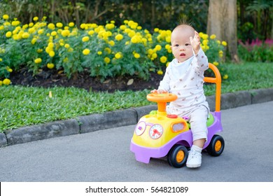 Asian little cute toddler baby boy learn to ride his first bike in park, Kid drive a car toy in garden with beautiful yellow and pink flowers, Child waving hello hand up, Kid first experience concept