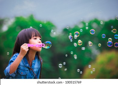 Asian little girl is blowing a soap bubbles
