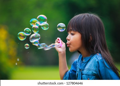 Asian little girl is blowing a soap bubbles, Outdoor Portrait