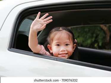 Asian little girl in car smiling and looking camera sitting on a backseat of a car waving goodbye. Transportation concept.
