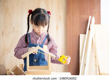 Asian little girl carpenter working on woodworking table in home carpenter shop.